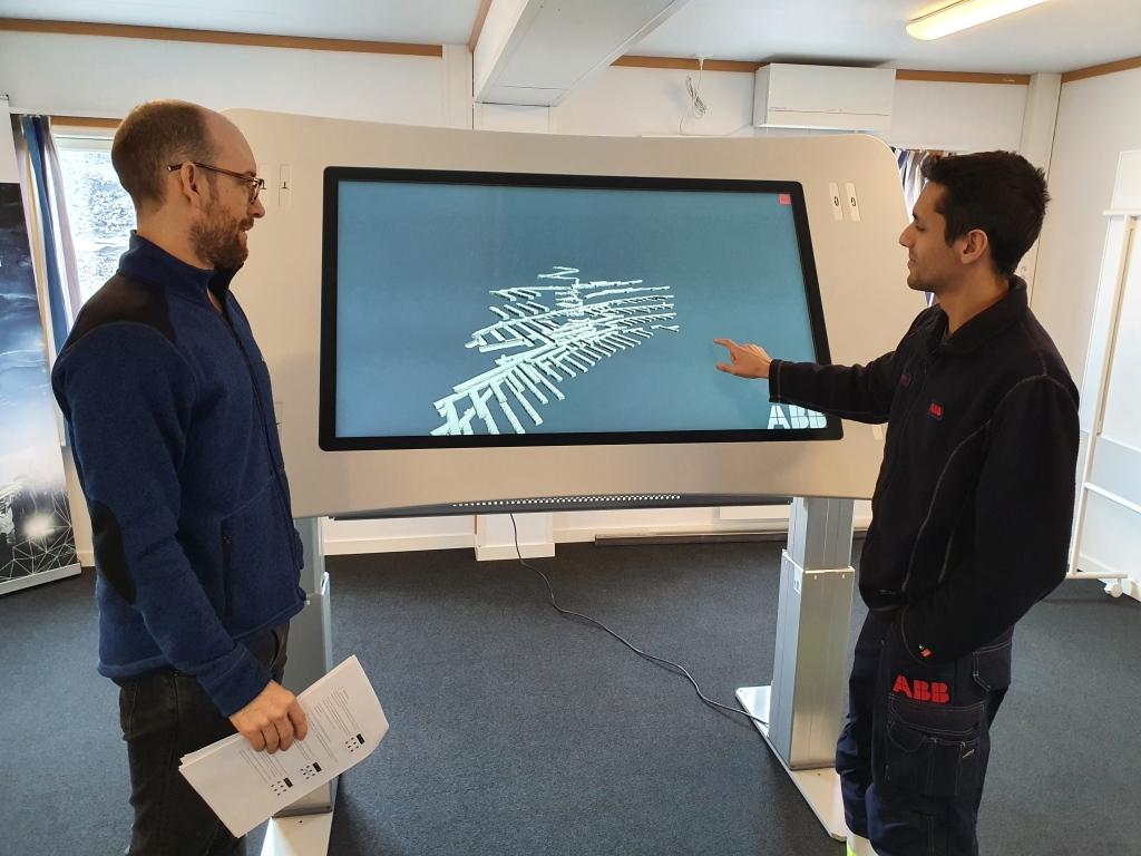 Två män står vid en stor skärm i ett kontor.