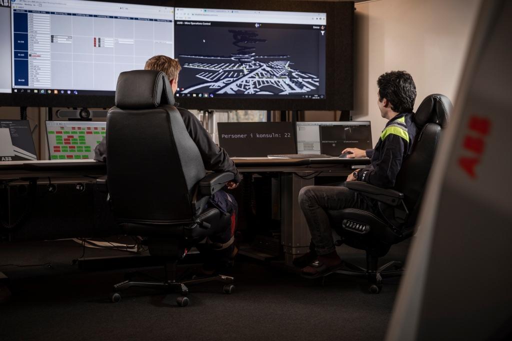 Kontor med stora skärmar och två personer som arbetar